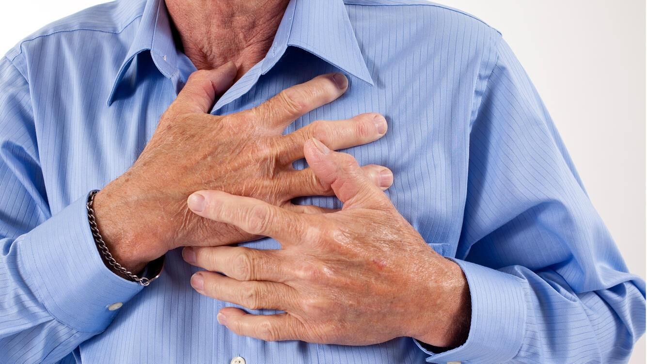 Senior adult man clutching his chest in pain. Heart attack, heart disease. He wears a medical alert bracelet and blue dress shirt.